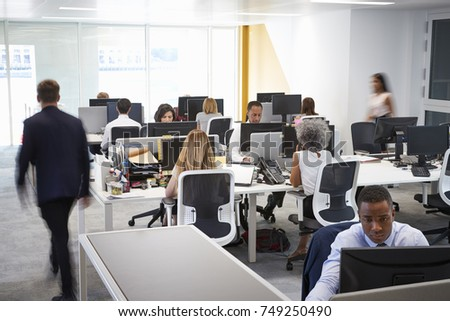 Man walking through a busy open plan office