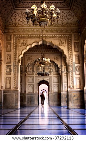 Man walking through archway in Badshai Mosque, Lahore, Pakistan - stock photo