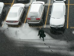 Man walking to car in snow.