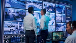 Man walking towards colleague with tablet and discussing surveillance footages on large screen while working in security center
