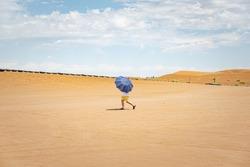 Man walking under umbrella in Kumtag desert in Northwestern China near ShanShan, one of the hottest regions worldwide.