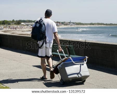 man walking with cooler to beach