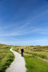Man walking with dog in dunes at the coast