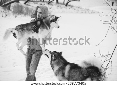 Man walking with dog winter time with snow in forest Malamute and Huskies friendship black and white