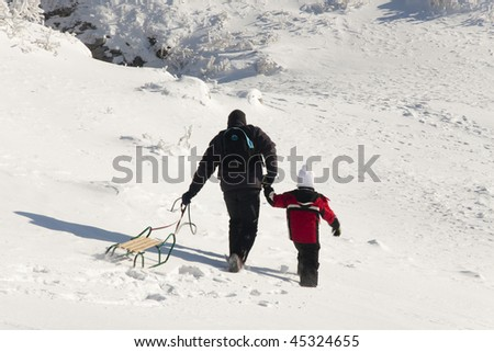 Man walking with sled. Winter sunny day.
