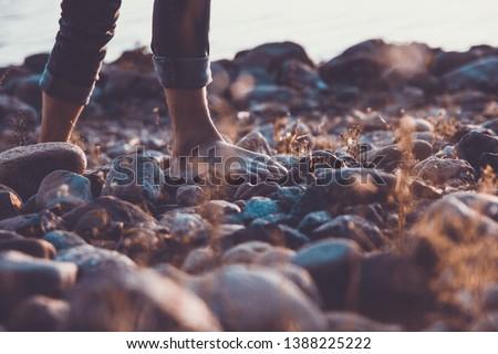 man walks barefoot on the beach of stones on the seashore ストックフォト ©