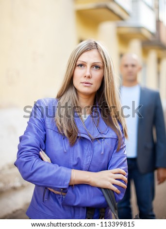 Man walks behind woman on the city street
