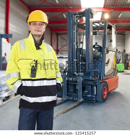 Man waring safety clothes including a hard hat standing proudly in front of his forklift truck in a warehouse