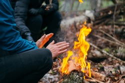 Man warms his hands on fire. Burning wood at evening in the forest. Campfire at touristic camp at nature. Barbeque and cooking outdoor fresh air. Flame and fire sparks on dark abstract background