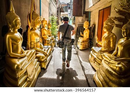 Man was walking through golden buddha road.Bangkok Thailand.