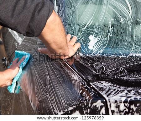 Man washing a black car with a cloth