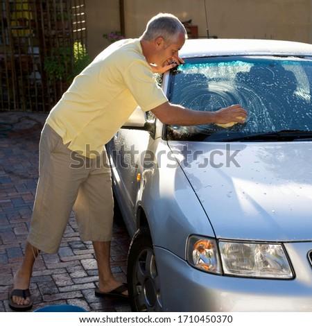 Man washing a car on a sunny day