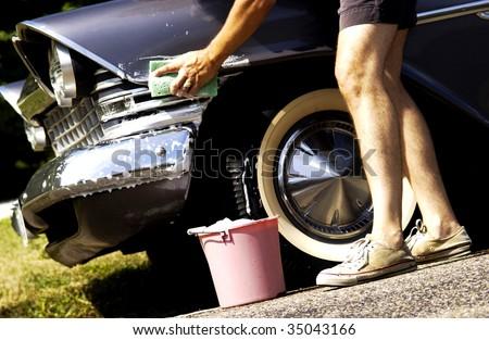 man washing antique car