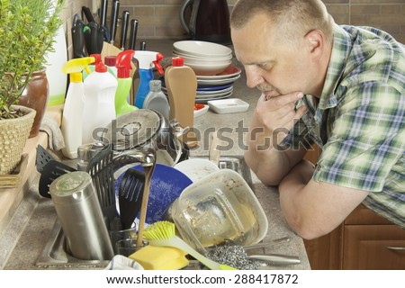 Man washing dirty dishes in the kitchen sink. Domestic cleaning up after the party.
