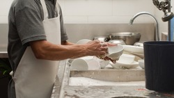 Man washing dish on sink at restaurant