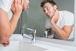 Man washing face in sink in bathroom rinsing after shaving. Home lifestyle copy space.