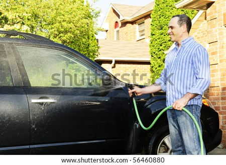 Man washing his car on the driveway