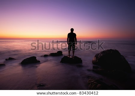 Man watch colorful sunrise from rocks near the beach; Bulgarian Black sea beautiful morning;