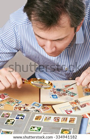 Man watching a collection of  stamps