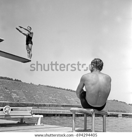 Man watching a high diver prepare to do backward flip off diving board #694294405