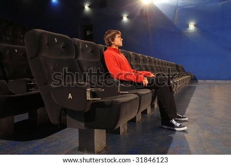 man watching a movie in a cinema