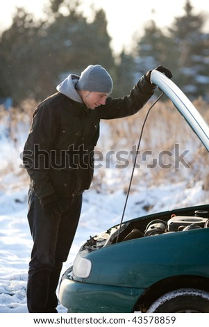 Man watching engine of broken car in winter