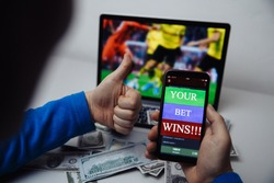 Man watching football match online broadcast on his laptop and holds smartphone with online gambling application and winning message