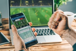 Man watching football play online broadcast on his laptop, cheering for his favourite team, making bets at bookmaker's website.