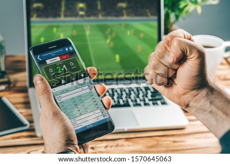Man watching football play online broadcast on his laptop, cheering for his favourite team, making bets at bookmaker's website. Foto stock ©