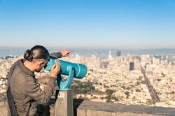 Man watching Francisco Downtown on a binocular from Twin Peaks
