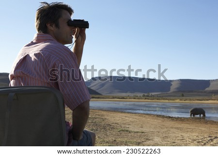 Man Watching Hippos on Safari