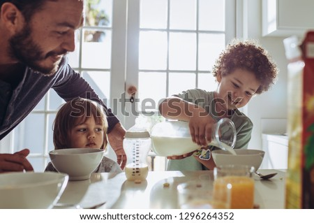 Man watching his kid pour milk in his breakfast bowl. Father and kids sitting at the table preparing breakfast.