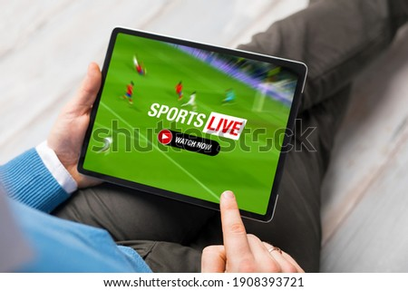 Man watching live stream of football match on tablet