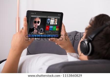 Man watching movie on website through digital tablet