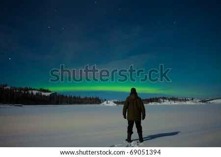 Man watching Northern Lights (Aurora borealis) over moon lit snowscape of frozen lake and forested hills.