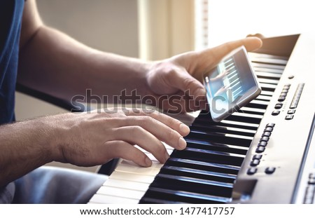 Man watching piano tutorial video with mobile phone. Person practising playing with an online lesson and course. Internet class to learn a new instrument. Pianist training with smartphone. #1477417757