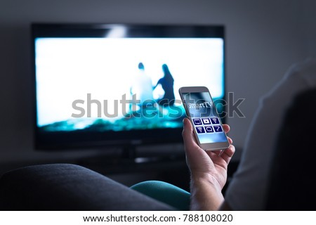 Man watching television and using smart tv remote control application on mobile phone. Choosing movie stream, switching channel or changing settings in the menu and user interface with smartphone.