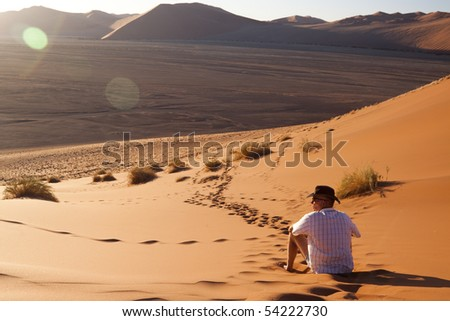 Man watching the sun go down on a sand dune