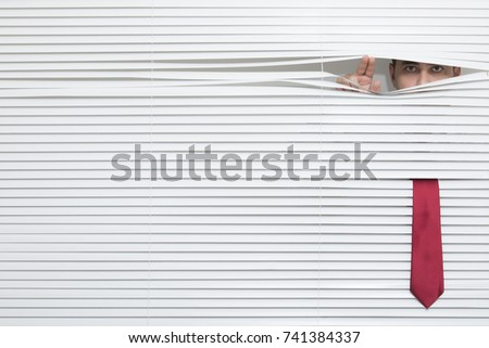 Man Watching through window blinds #741384337