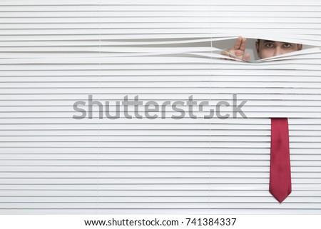 Man Watching through window blinds #741384337