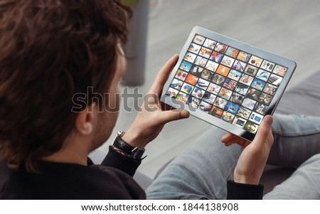 Photo of  Man watching TV on tablet. Television, multimedia streaming services