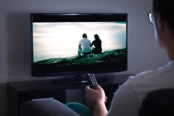 Man watching tv or streaming movie or series with smart tv at home. Film or show on television screen. Person holding the remote control or switching channel. Turning on or off tv.