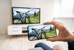 Man Watching TV Streaming From Smartphone Or Mobile Phone