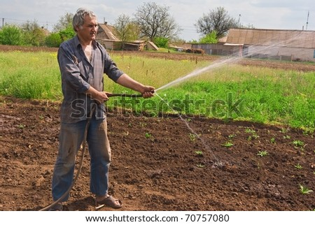 man watering a field