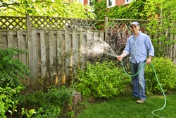 Man watering the garden with hose in backyard
