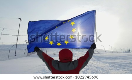 Man waving a flag of the European Union in winter on a ski slope #1022945698