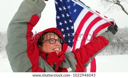 Man waving a flag of the united states in winter on a ski slope #1022946043