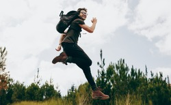 Man wearing a backpack jumping in air while trekking in the woods. Excited man on a holiday hiking in a countryside location.