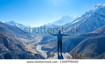 Man wearing a beanie and blue jumper, spreads his arms wide, breathing deeply the fresh mountain air. His gesture represents freedom and happiness. Below a long valley stretches in Himalayas.