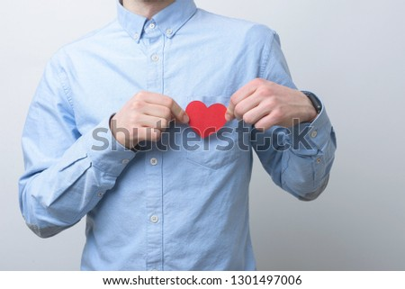Man wearing a blue shirt is holding a small red heart above his chest. Caring and loving concept. #1301497006